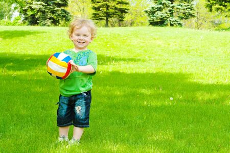 Smiling little boy with a ball in the park photo
