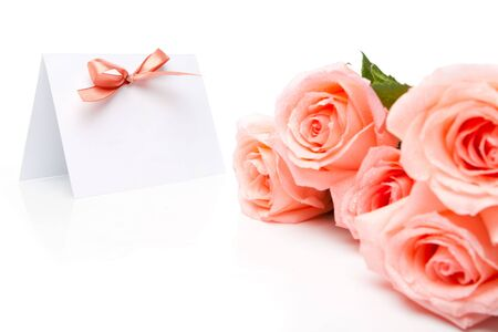 Invitation card in focus and a bunch of roses photo