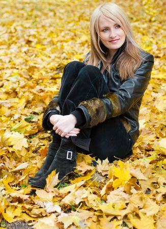 Smiling girl sitting in the autumn leaves photo