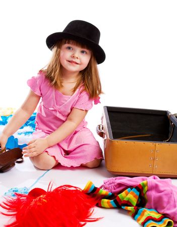 Attractive little girl in hat packing an old suitcase photo