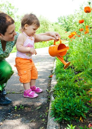 Mother and daughter watering plants in the garden photo