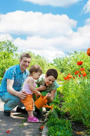 Family watering flowers in their garden Stock Photo - 5024650