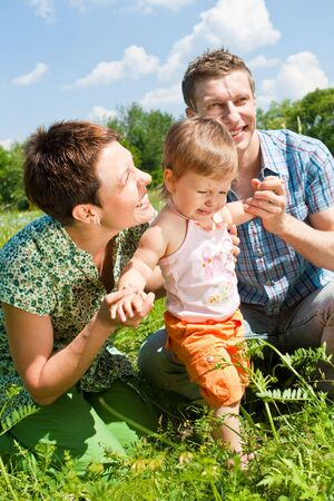 Happy family in the green sunny meadow photo