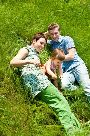 Family lying in the green meadow grass Stock Photo - 5031372