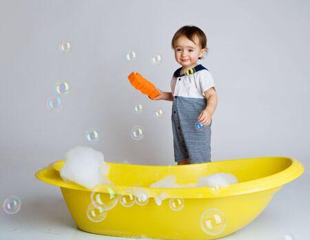 Baby with sponge standing beside yellow bathtub photo