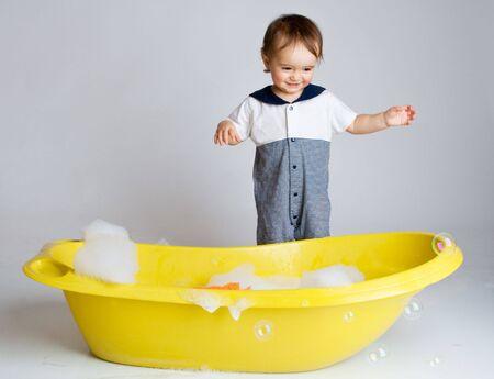 Charming baby standing near bathtub ready to take bath photo