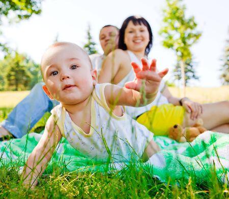bebe gateando: Rastreo beb� y sus padres detr�s, se centran en beb� Foto de archivo
