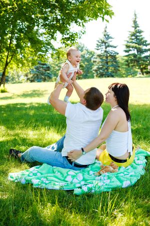 Family sitting  in the summer park  and playing photo