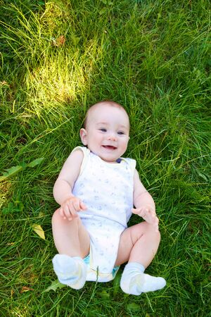 Smiling baby lies in the green grass photo