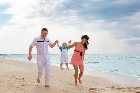 Happy family running along the summer beach photo