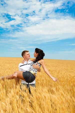 Man standing in the wheat field with a beautiful woman on hands photo