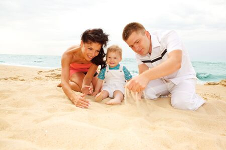 Mother, father and baby playing on the beach Stock Photo