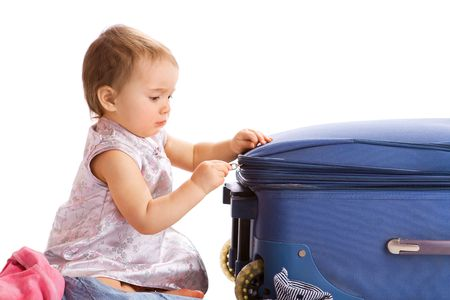 Cute baby zipping the suitcase for summer vacations, isolated photo