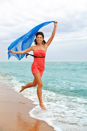 barefooted: Happy barefooted  woman running along the beach