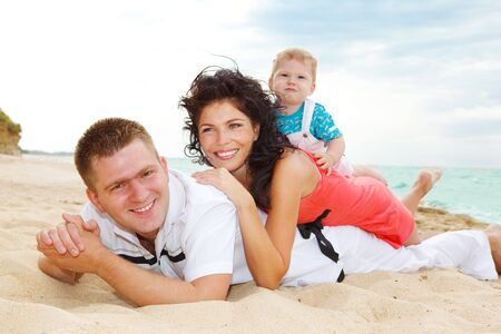 Laughing family lying on the sand in summer Stock Photo - 5134048