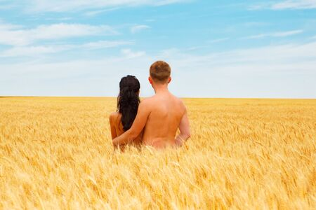 Couple standing in a wheat field looking far away Stock Photo - 5134042