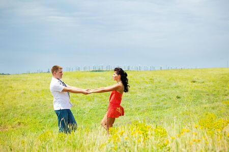 A happy couple holding hands in the meadow, wind turbines in the background Stock Photo - 5173204