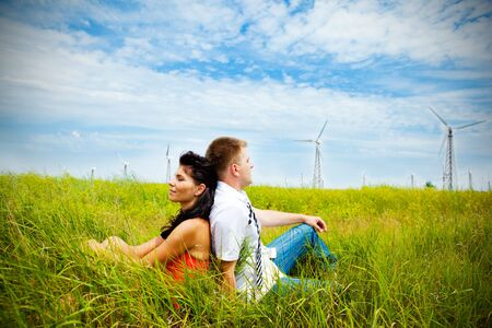 Couple having rest in the meadow with wind turbines Stock Photo - 5175790