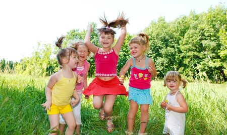 Five little preschool friends jumping in the grass Stock Photo - 5175788