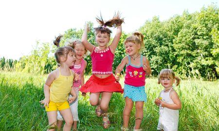Five little preschool friends jumping in the grass