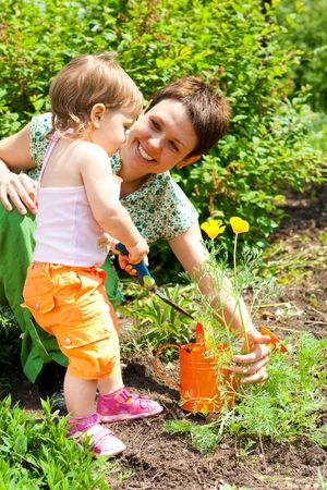 girl helping mother in the garden photo