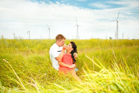 Romantic couple sitting in the meadow, wind turbines behind them Stock Photo - 5175801