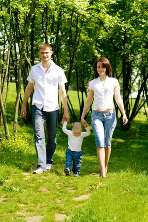 Mother, father and baby walking along the photo