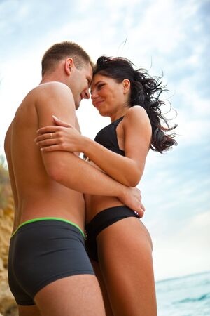 Happy couple hugging on the beach photo