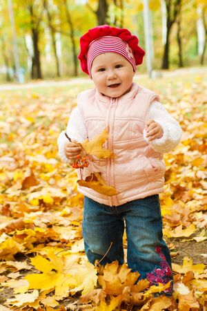 Happy toddler walking in the autumn park photo