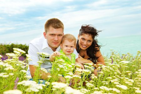 Happy young parents and their son on hill photo