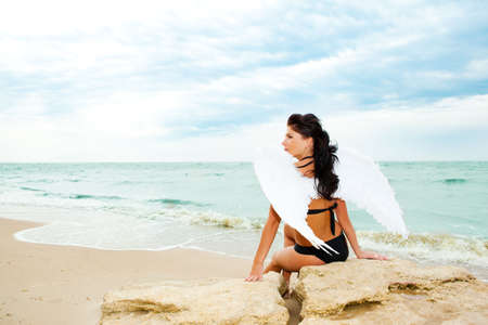 Lonely angel sitting on a rock at the beach Stock Photo - 5210811