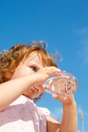 Beautiful curly girl drinking water from a glass photo