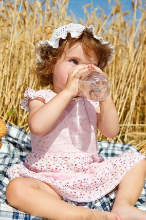 Toddler drinking water in a wheat field photo
