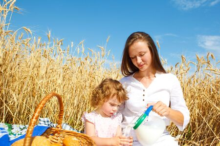 Mother and daughter having breakfast in the wheat field Stock Photo - 5210809