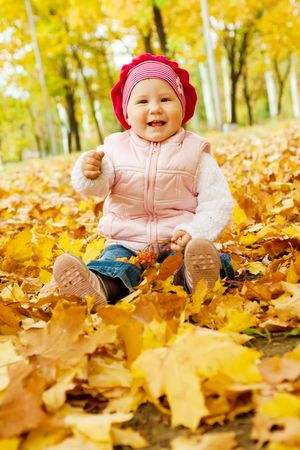 Laughing kid sits in an autumn park photo