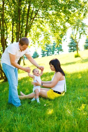 Baby making first steps with the help of his parents Stock Photo - 5247539