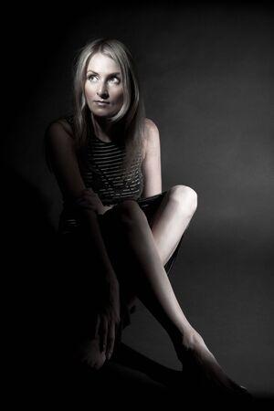 Girl sitting in spot of light over black photo