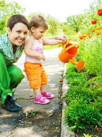 Mother and daughter watering flowers in the garden Stock Photo - 5295586