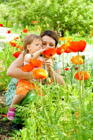 Mother showing flowers to her little daughter photo