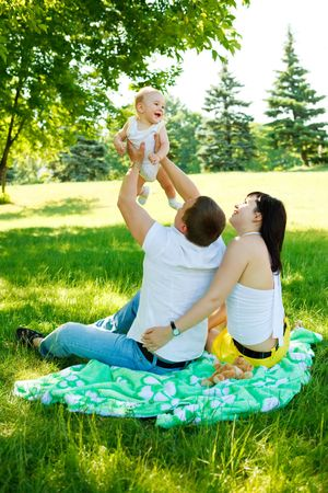 Happy parents playing with their baby in the park photo