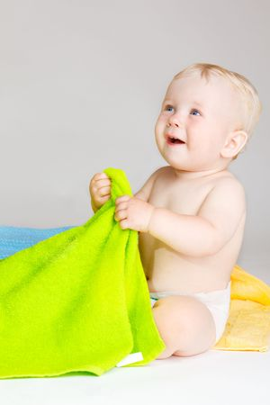 Joyful baby with colorful towels Stock Photo - 5362038