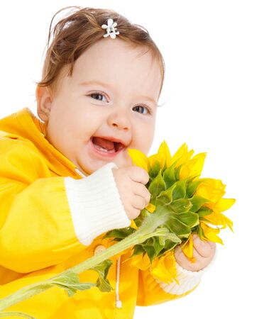 Portrait of a laughing baby with sunflower in hands photo