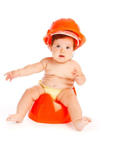 Baby in hardhat sitting on the potty photo