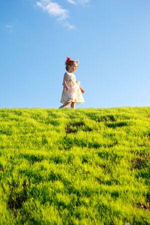 Little girl on green grass hill over blue sky photo