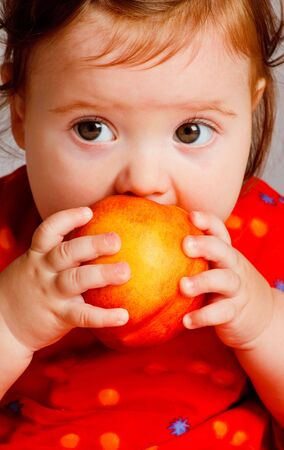 Closeup portrait of a baby eating a peach photo