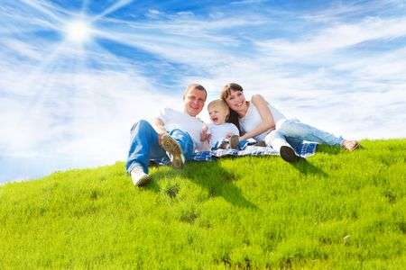 Beautiful cheerful family sitting on the green hill Stock Photo - 5484160