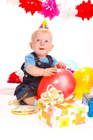 Baby with birthday presents and balloons photo