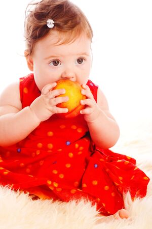 Baby girl with a large peach in hands photo