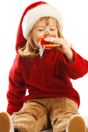 Sweet preschool girl biting a chocolate bar photo