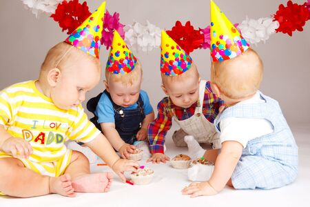 Four babies taking their birthday cakes photo